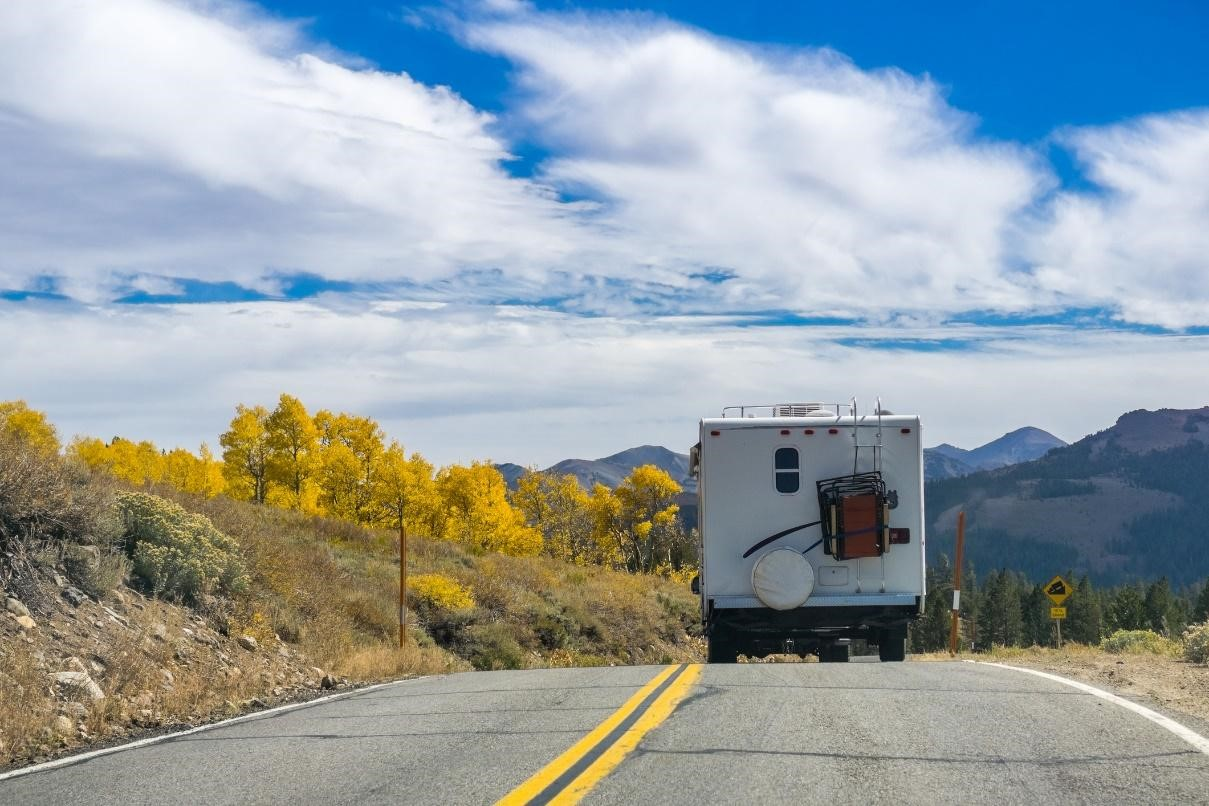 RV driving down a scenic road during the fall