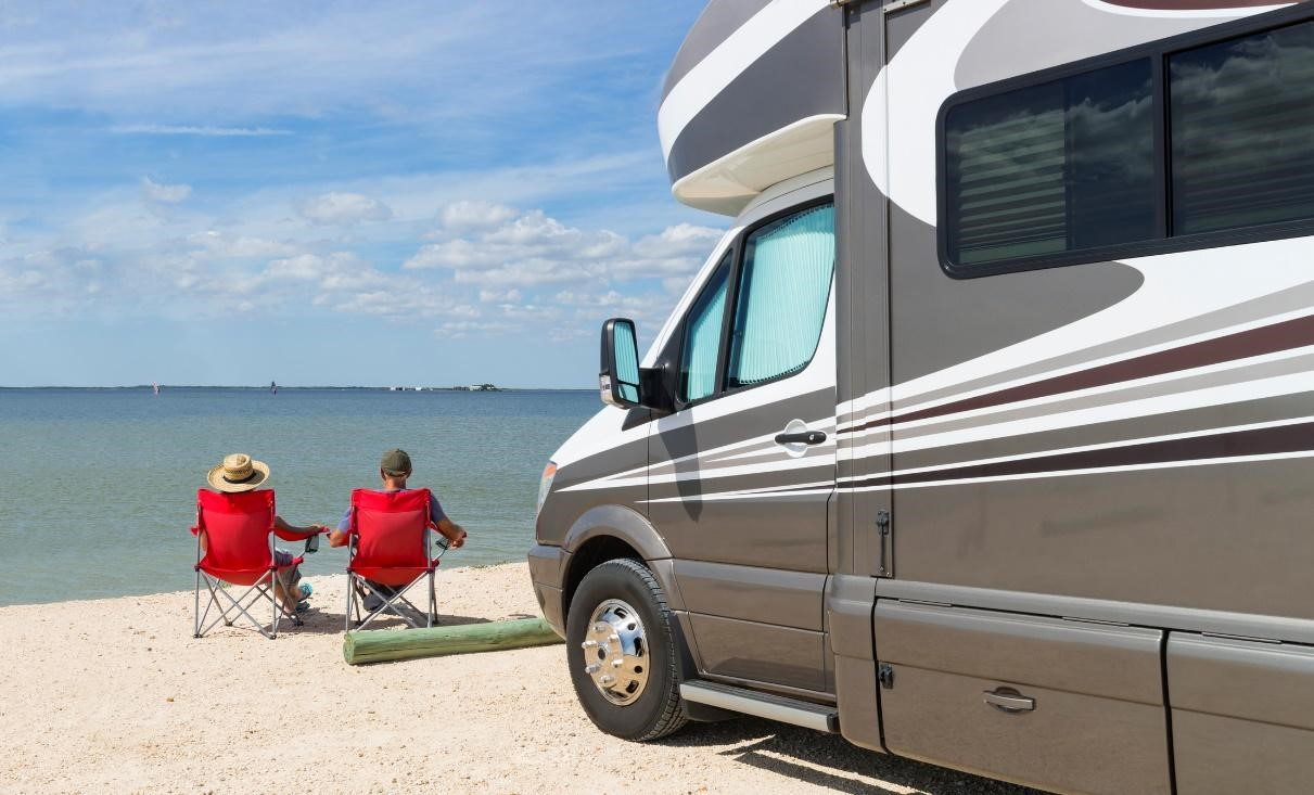 couple hanging out on the beach next to their Class C RV