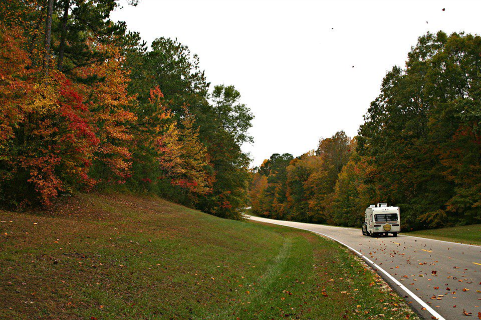 RV driving through fall foliage