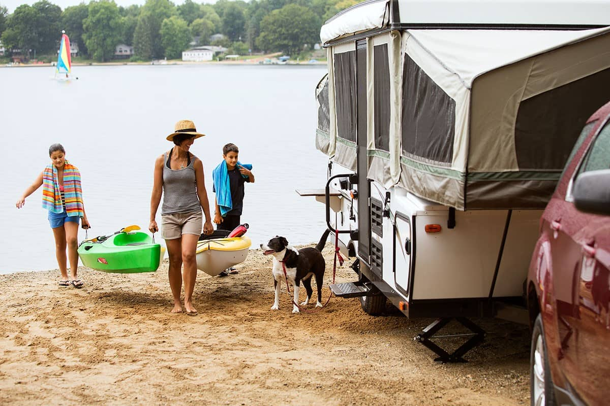 family of woman with kids dog and pop up camper kayaking