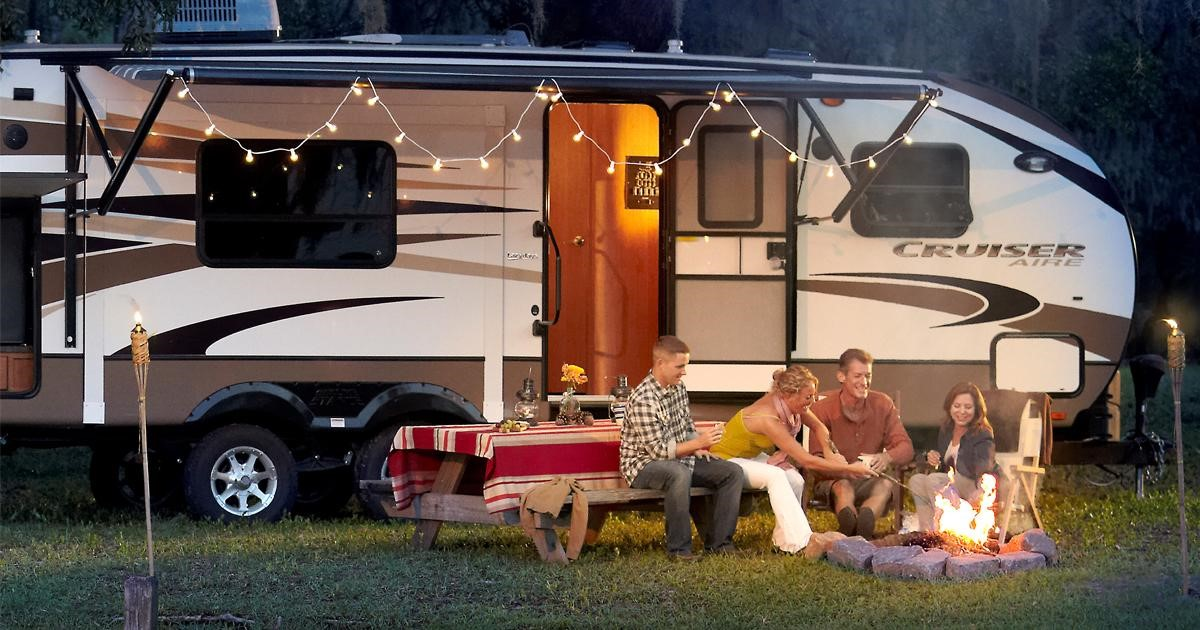 Family next to a fire, outside their RV.